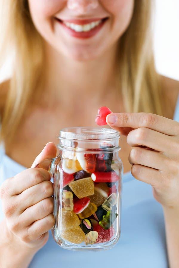 Mujer joven hermosa que sostiene el amor rojo y el vidrio llenos de dulces sobre el fondo blanco imágenes de archivo libres de regalías