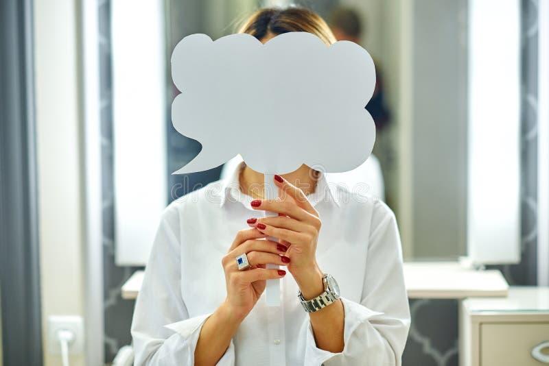 Mujer joven hermosa que sostiene el anuncio en blanco del espacio de la copia de la tarjeta de la muestra delante de su cara foto de archivo