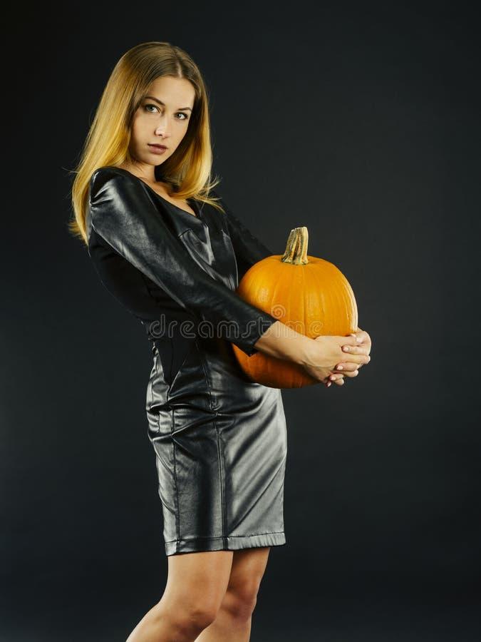 Mujer joven hermosa que sostiene la calabaza para Halloween foto de archivo