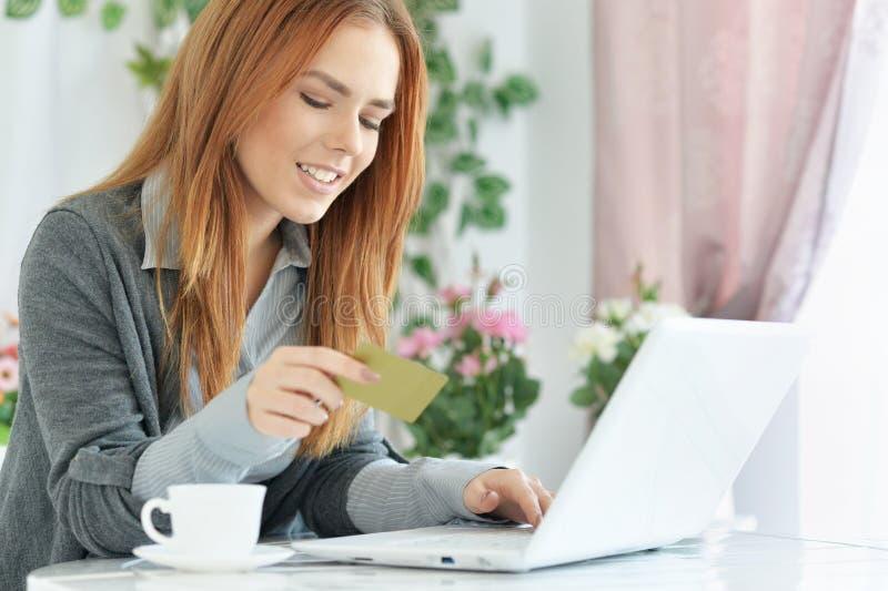 Mujer joven hermosa que sostiene la tarjeta de crédito y que usa el ordenador portátil foto de archivo