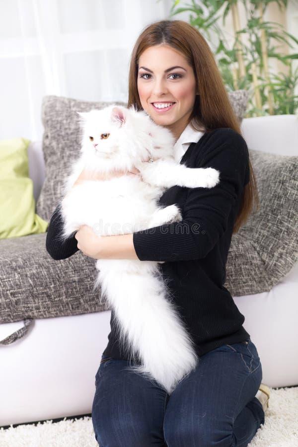 Mujer joven hermosa que sostiene un gato persa imagenes de archivo