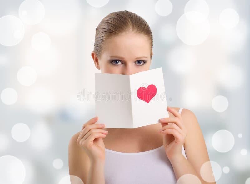 Mujer joven hermosa que sostiene una postal de la tarjeta del día de San Valentín foto de archivo