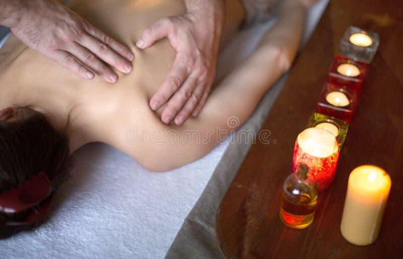 Mujer joven hermosa que tiene masaje en un salón del balneario fotografía de archivo