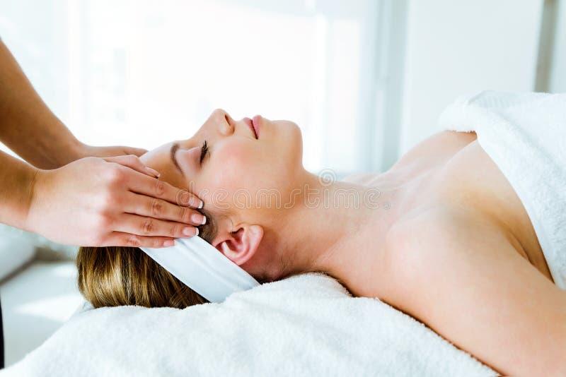 Mujer joven hermosa que tiene masaje facial del balneario en salón de belleza fotografía de archivo