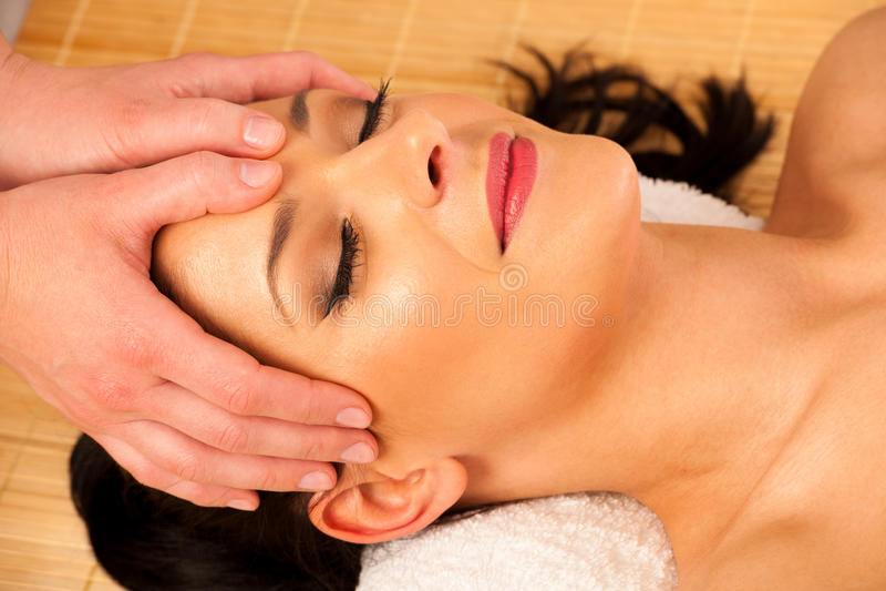 Mujer joven hermosa que tiene un masaje de cara en estudio de la salud fotos de archivo libres de regalías