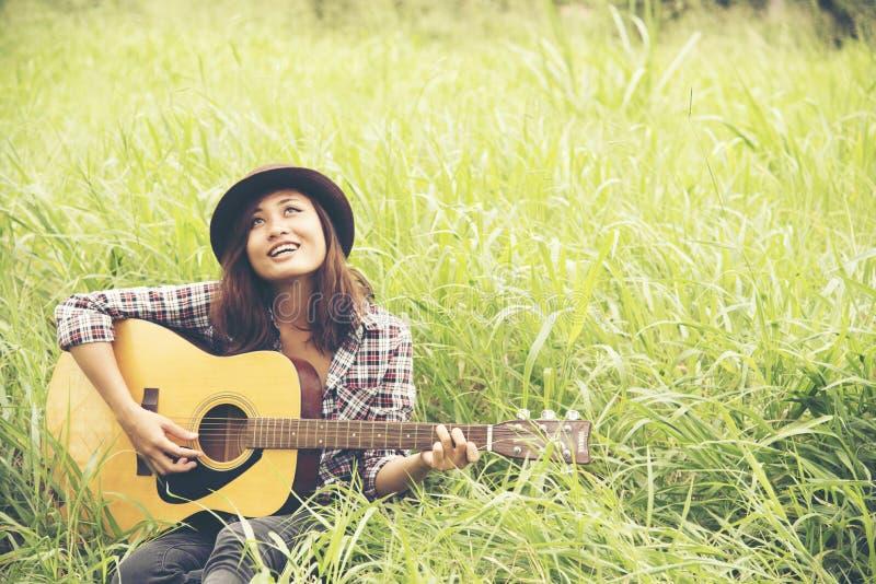 Mujer joven hermosa que toca la guitarra en el prado verde fotografía de archivo