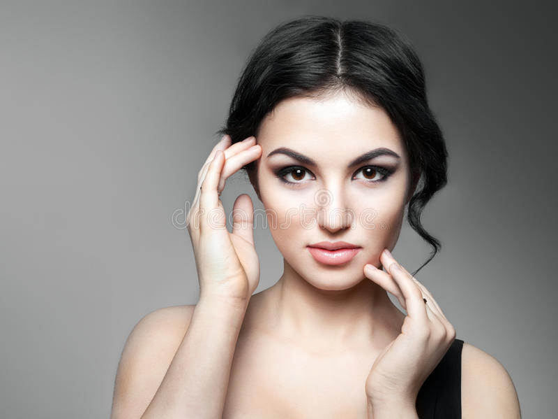 Mujer joven hermosa que toca su cara fotografía de archivo libre de regalías