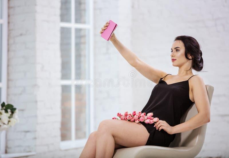 Mujer joven hermosa que toma el selfie con la tableta digital dentro foto de archivo