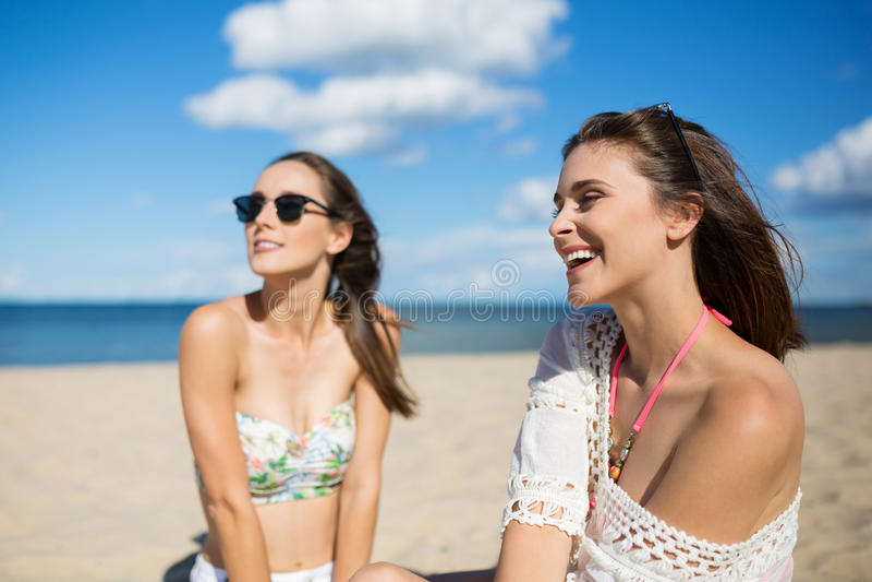 Mujer joven hermosa que toma el sol con la risa del amigo foto de archivo libre de regalías