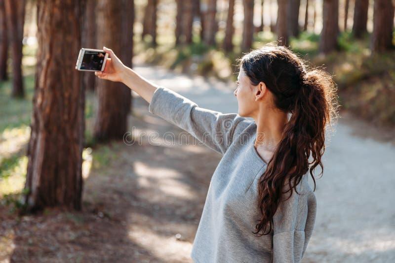Mujer joven hermosa que toma la foto con el teléfono móvil self Vlog Llamada video foto de archivo libre de regalías