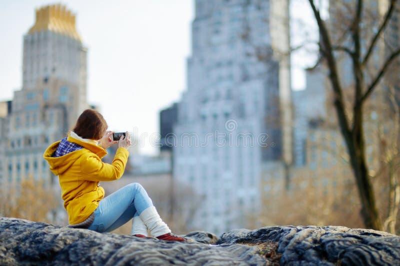 Mujer joven hermosa que toma una foto de skyscapers foto de archivo libre de regalías