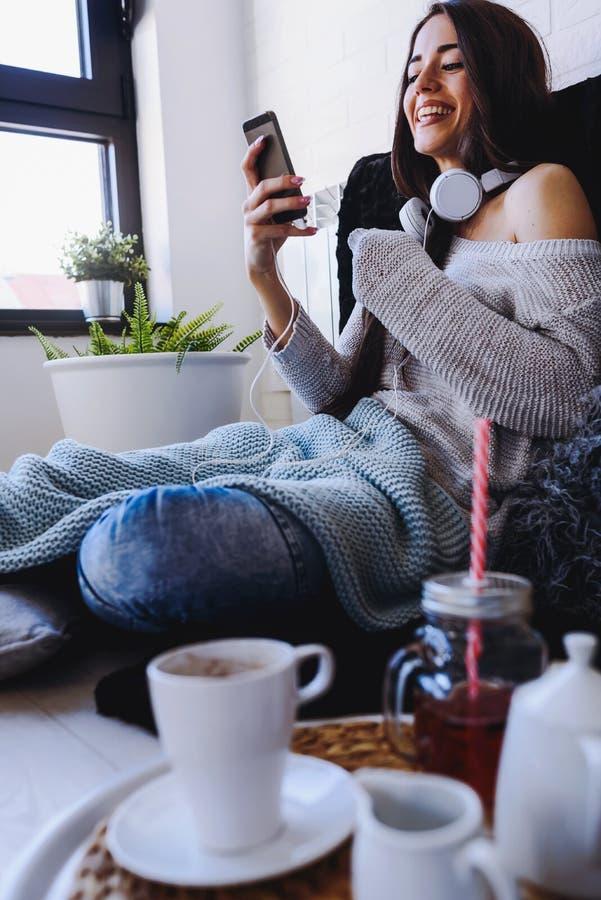 Mujer joven hermosa que usa el teléfono elegante en casa en la mañana imágenes de archivo libres de regalías