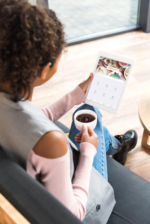 mujer joven hermosa que usa la tableta con el forsquare app imagen de archivo