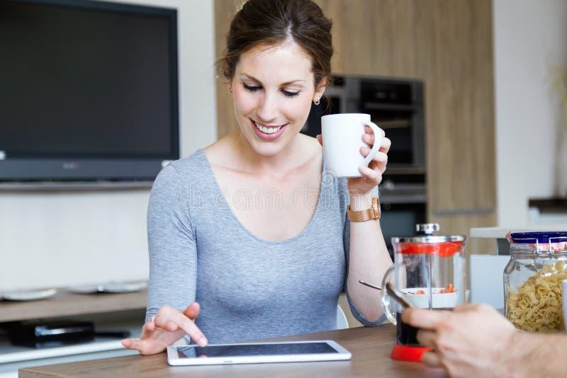 Mujer joven hermosa que usa su tableta digital mientras que goza del desayuno en la cocina foto de archivo