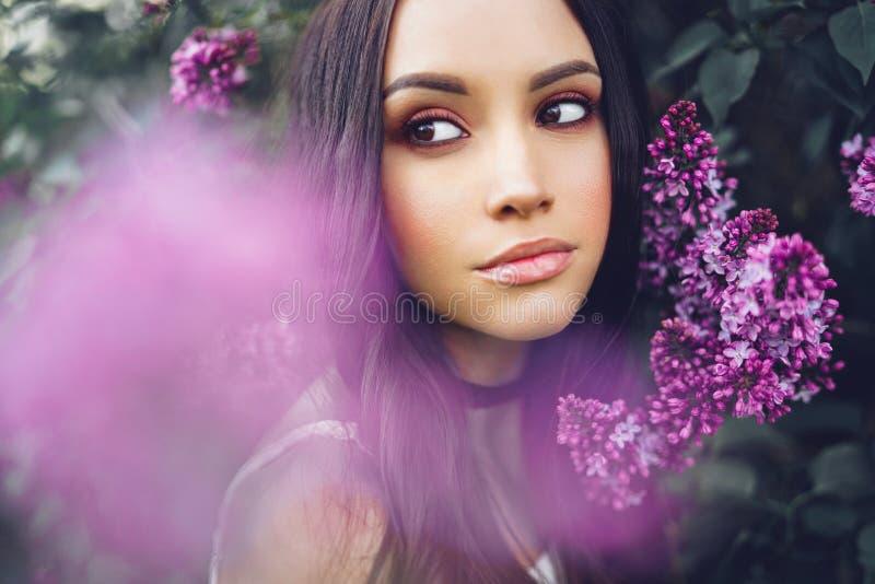 Mujer joven hermosa rodeada por las flores de la lila fotografía de archivo libre de regalías
