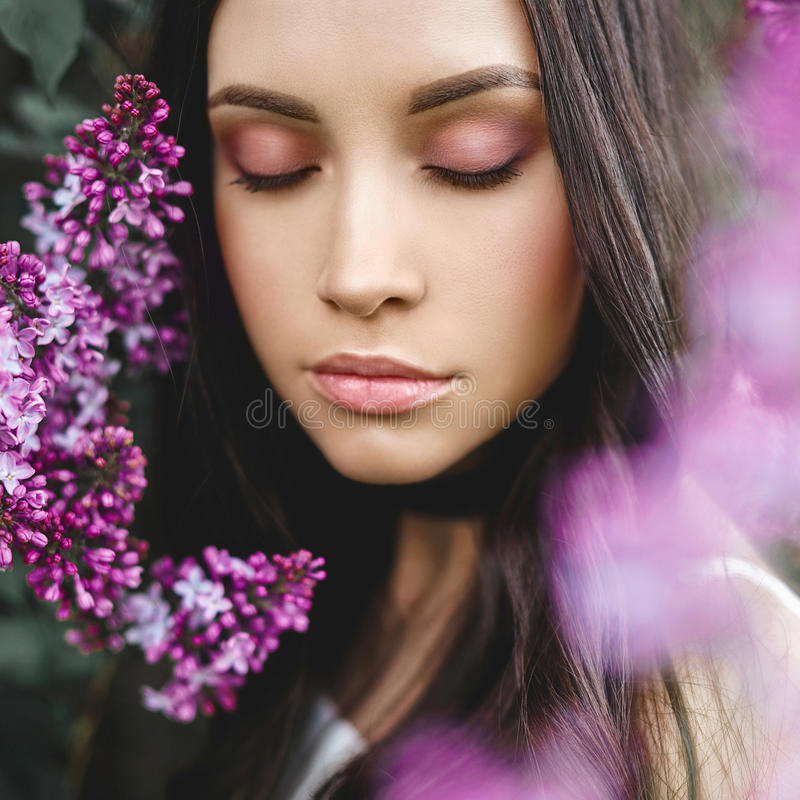 Mujer joven hermosa rodeada por las flores de la lila foto de archivo