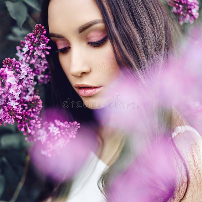 Mujer joven hermosa rodeada por las flores de la lila fotografía de archivo