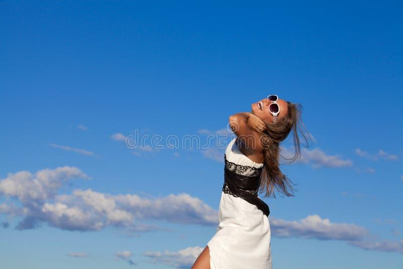 Mujer joven hermosa sobre el cielo azul imágenes de archivo libres de regalías