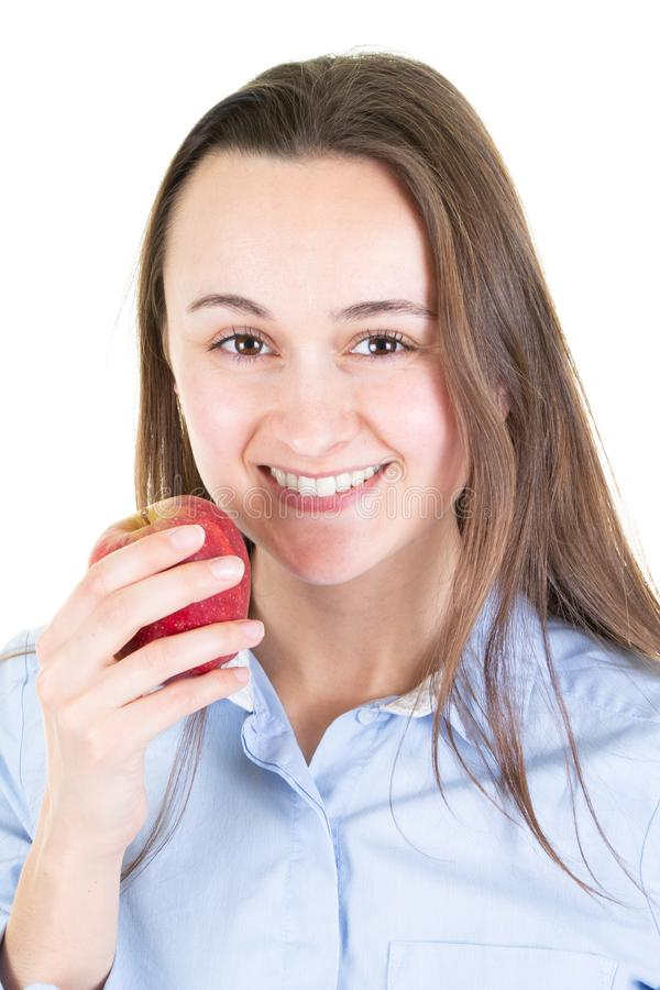 Mujer joven hermosa sobre la pared blanca que come la manzana roja con la situación feliz de la cara y que sonríe con una sonrisa imagenes de archivo