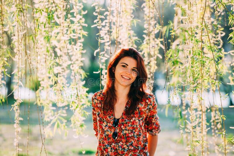 Mujer joven hermosa, sonriendo bajo ramas fotos de archivo libres de regalías