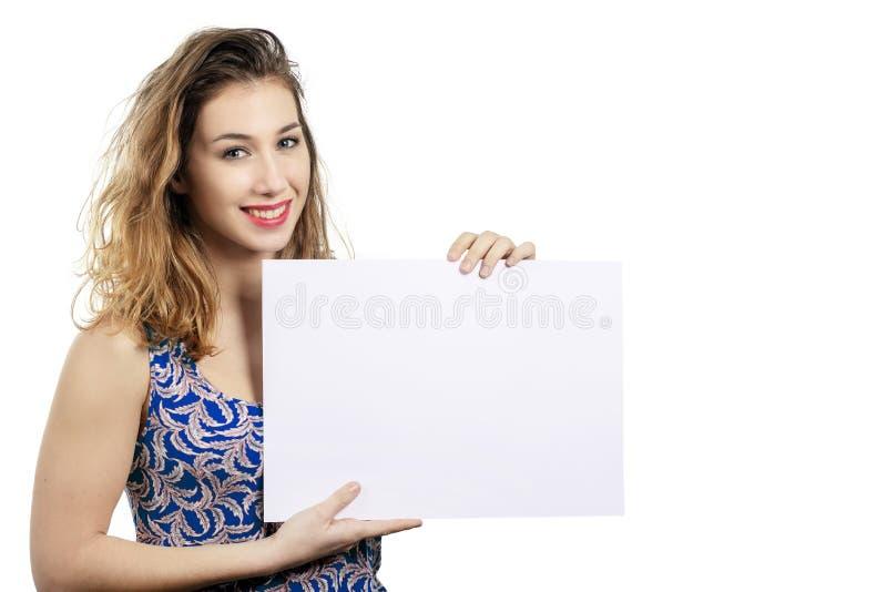 Mujer joven hermosa sonriente feliz que muestra el letrero en blanco o c imagen de archivo