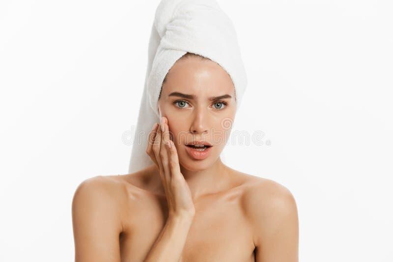Mujer joven hermosa sorprendida después del baño que toca su cara con una toalla en su cabeza aislada en fondo azul piel imagen de archivo