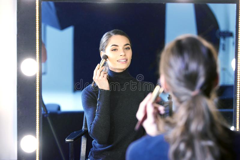 Mujer joven hermosa usando cepillo mientras que aplica su makup imagen de archivo libre de regalías