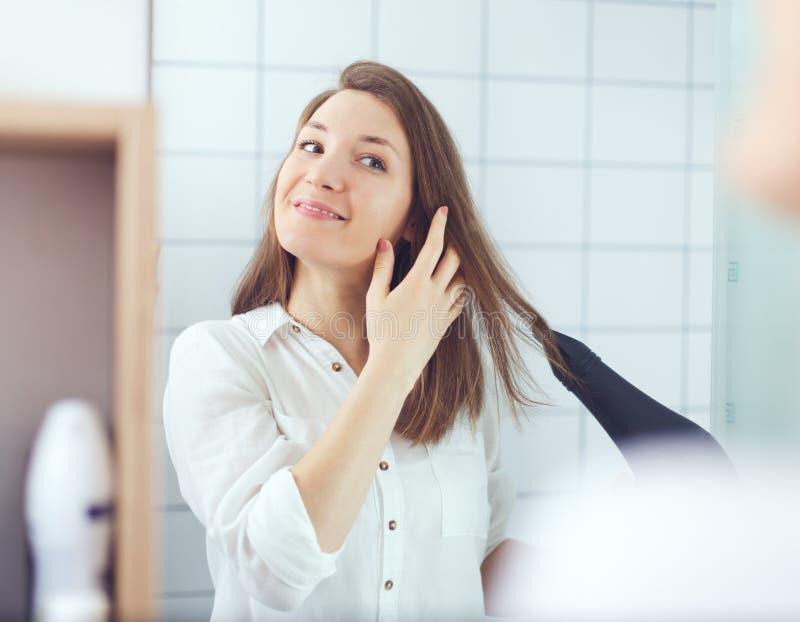 Mujer joven hermosa usando el cabello seco del secador de pelo Cuidado del cabello imagen de archivo