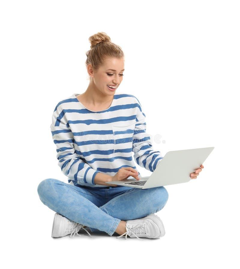 Mujer joven hermosa usando el ordenador portátil en blanco imagen de archivo