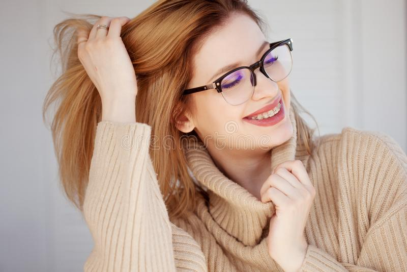 Mujer joven hermosa y elegante en suéter y vidrios de gran tamaño beige fotografía de archivo