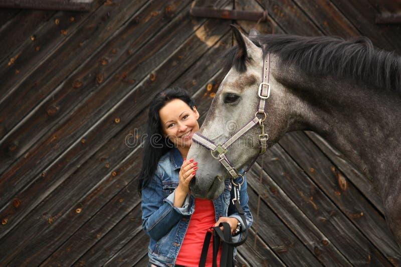 Mujer joven hermosa y retrato gris del caballo fotografía de archivo