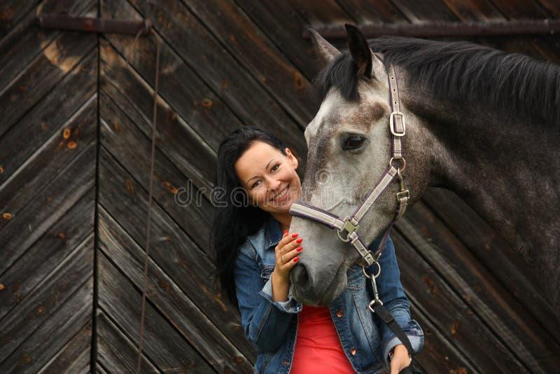 Mujer joven hermosa y retrato gris del caballo imagen de archivo