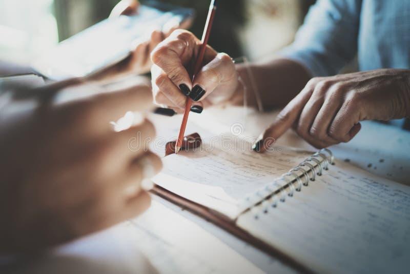 Mujer joven hermosa y su escritura del socio algo en cuaderno de notas mientras que se sienta en la butaca en la sala de estar ch foto de archivo
