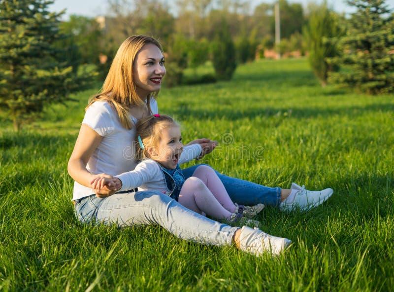 Mujer joven hermosa y su pequeña sentada de la hija imagenes de archivo