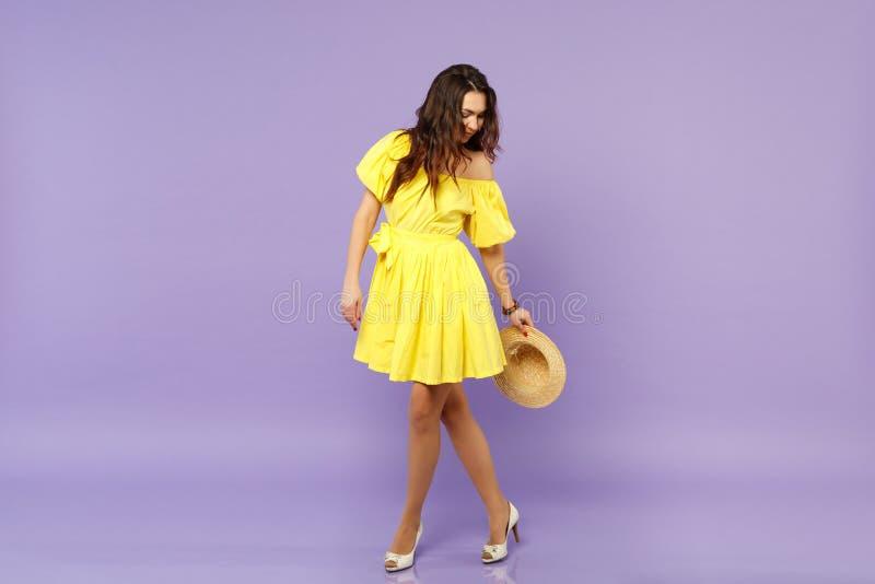 Mujer joven imponente en el vestido amarillo que sostiene el sombrero del verano, colocación, mirando abajo de aislado en la pare fotos de archivo
