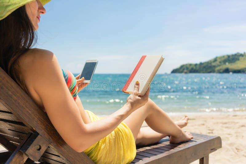 Mujer joven indecisa entre la lectura de un libro y pasar tiempo en Internet fotos de archivo
