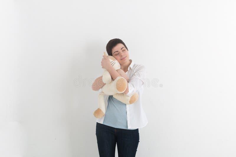 Mujer joven infantil que abraza el gato suave de la felpa con sonrisa inocente y los ojos cerrados Sueños dulces foto de archivo libre de regalías