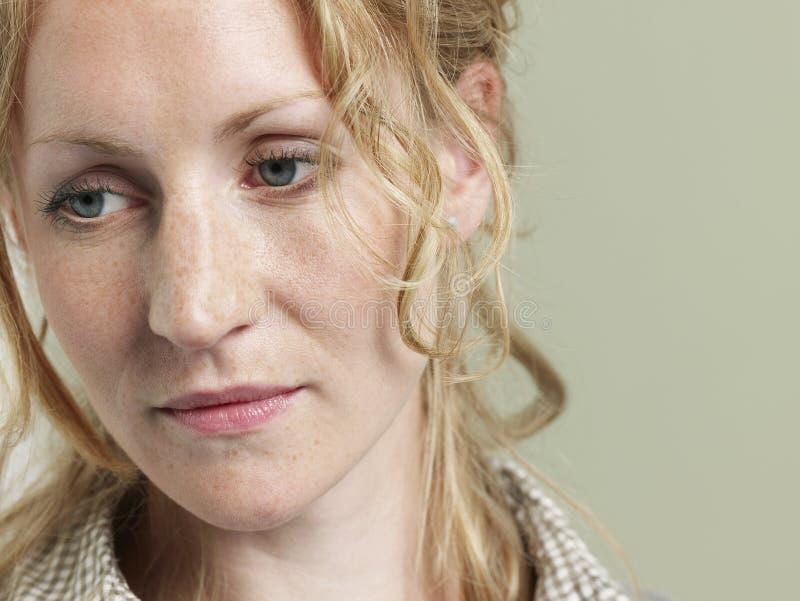 Mujer joven infeliz con el pelo ondulado imagenes de archivo