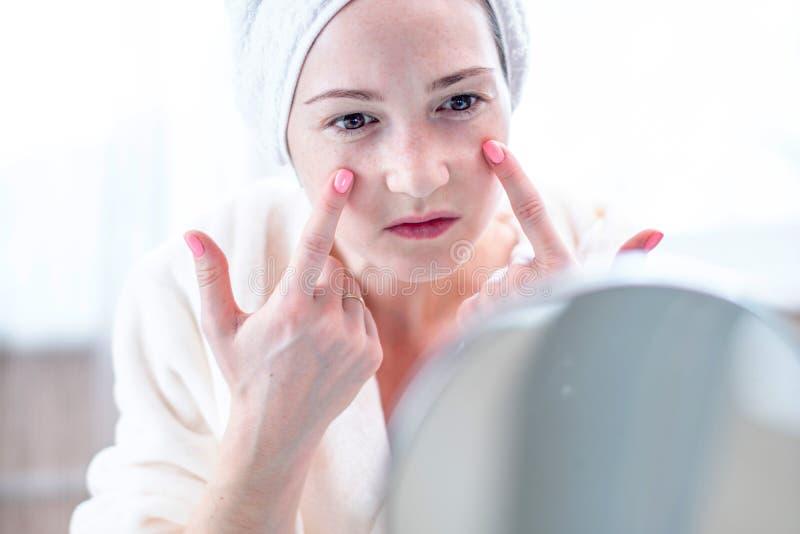 Mujer joven infeliz hermosa con una toalla en la cabeza que mira su piel en un espejo Higiene y cuidado oportunos para la piel imagen de archivo libre de regalías