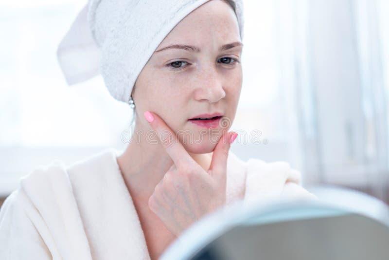 Mujer joven infeliz hermosa con una toalla en su cabeza que mira su piel en un espejo Higiene y cuidado para la piel foto de archivo libre de regalías