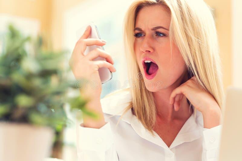 Mujer joven infeliz que habla en el teléfono fotos de archivo libres de regalías