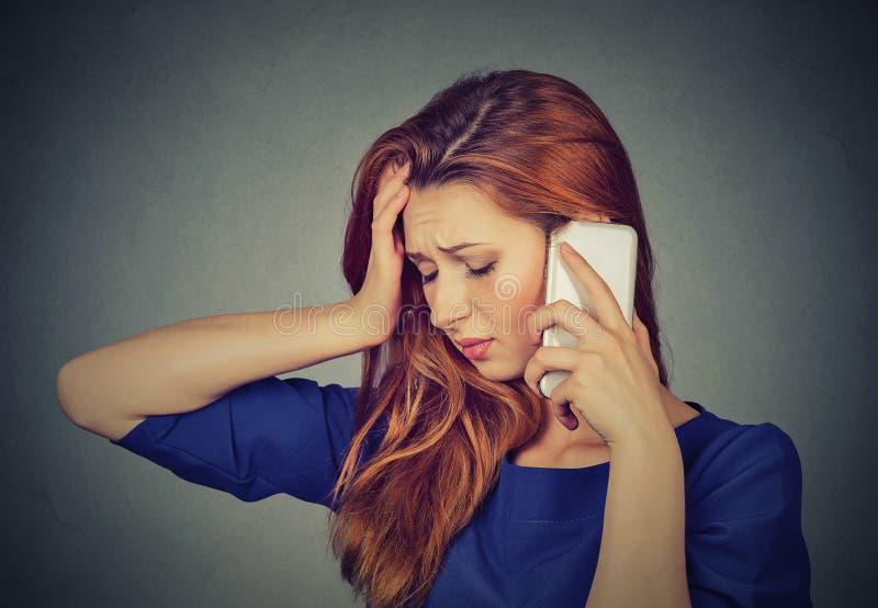 Mujer joven infeliz que habla en el teléfono móvil que mira abajo fotografía de archivo