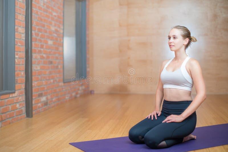 Mujer joven inspirada atractiva que se sienta en una estera de la yoga en un studi imagenes de archivo