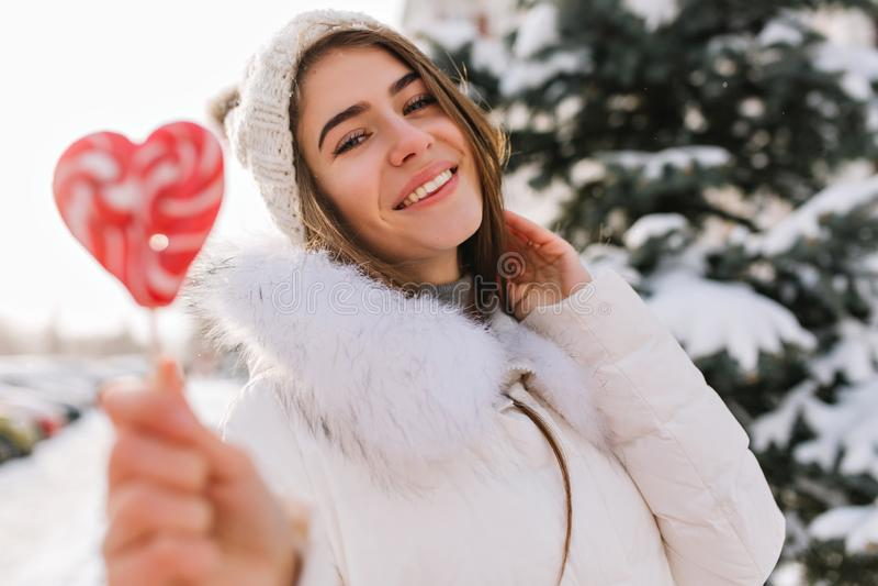 Mujer joven inspirada en el sombrero hecho punto blanco que se divierte con la piruleta rosada del corazón en la calle por comple fotos de archivo