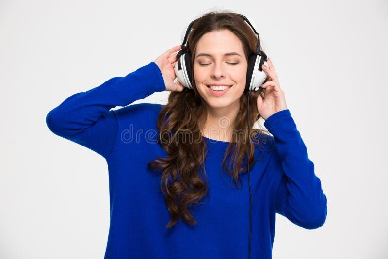 Mujer joven inspirada sonriente con los ojos cerrados que escucha la música foto de archivo