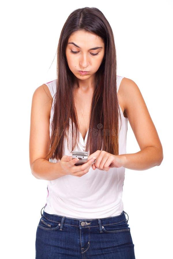Mujer joven irritada por el teléfono fotografía de archivo