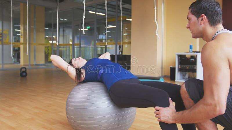 Mujer joven juguetona con el instructor de la aptitud que hace crujidos abdominales en fitballs foto de archivo