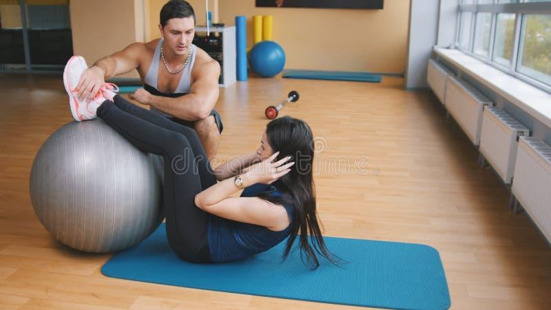 Mujer joven juguetona con el instructor de la aptitud que hace crujidos abdominales en fitballs fotografía de archivo