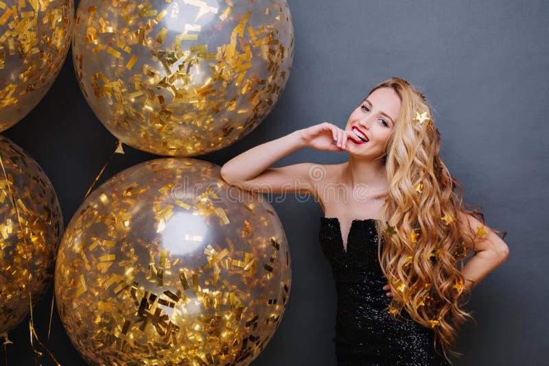 Mujer joven juguetona magnífica del retrato con el pelo rubio rizado largo que se divierte con los globos grandes llenos con mall foto de archivo libre de regalías