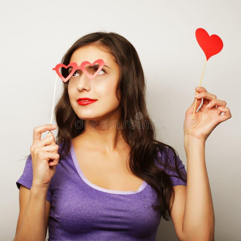 Mujer joven juguetona que sostiene los vidrios de un partido imagenes de archivo